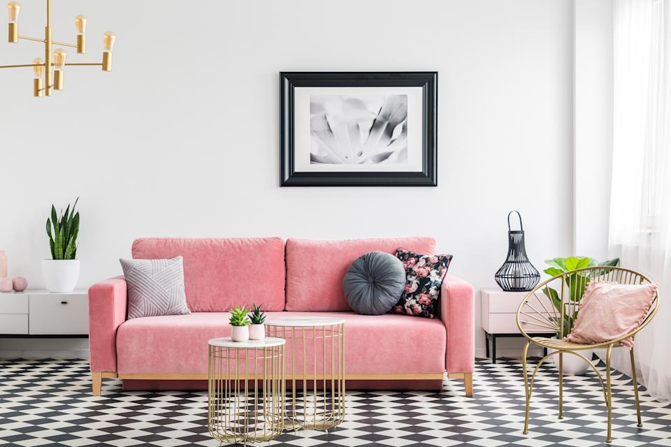 Glamor living room interior with a pink sofa, golden armchair and tables, poster and checkered tiles. Real photo