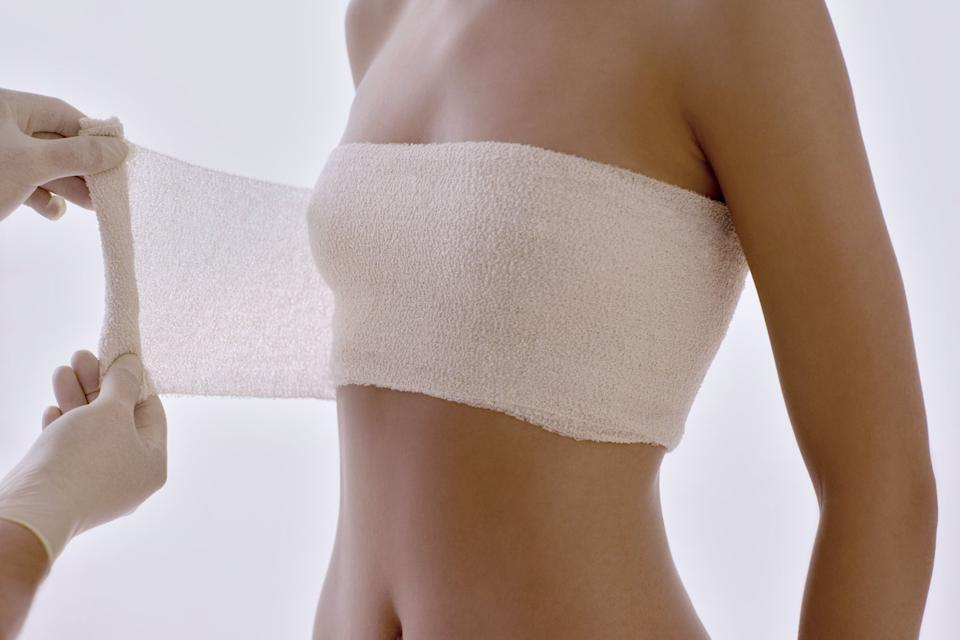 Cosmetic breast surgery. Cosmetic surgeon applying a protective bandage round the client's breasts after surgery.