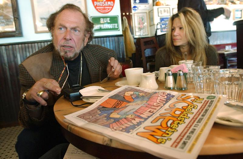 FILE - In this Oct. 28, 2003 file photo, Screw magazine publisher Al Goldstein sits for an interview at a coffee shop in New York with his longtime assistant Terre Galizio. Goldstein, the bird-flipping publisher who helped break down legal barriers against pornography and raged against politicians, organized religion and anything that even suggested good taste, died at a Brooklyn hospice Thursday, Dec. 19, 2013 after a long illness, according to a friend, attorney Charles C. DeStefano. He was 77. (AP Photo/Mary Altaffer, File)