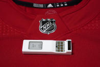 A sensor is shown with a Detroit Red Wings NHL hockey jersey, Tuesday, Oct. 5, 2021, in Detroit. The NHL is using real-time tracking technology in pucks and on the back of players' jerseys, shooting to generate more data for teams, broadcasters, fans and gamblers. (AP Photo/Paul Sancya)
