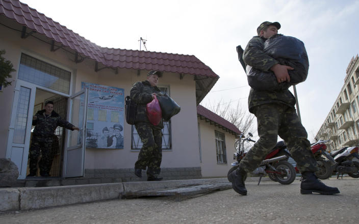 Ukrainian air force officers walk with their bags at the Belbek airbase, outside Sevastopol, Crimea, on Thursday, March 20, 2014. With thousands of Ukrainian soldiers and sailors trapped on military bases, surrounded by heavily armed Russian forces and pro-Russia militia, the Kiev government said it was drawing up plans to evacuate its outnumbered troops from Crimea back to the mainland and would seek U.N. support to turn the peninsula into a demilitarized zone. (AP Photo/Ivan Sekretarev)