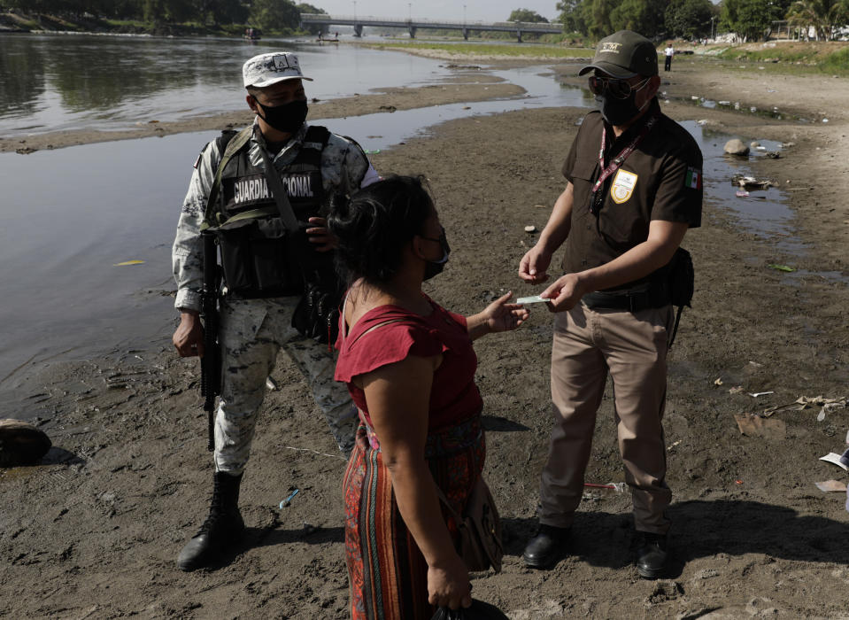 Mexican immigration agents review the identification of a Guatemalan woman at an access point to the Suchiate River, the natural border between Guatemala and Mexico, near Ciudad Hidalgo, Mexico, Sunday, March 21, 2021. Mexico sent hundreds of immigration agents, police and National Guard to its southern border to launch an operation to crack down on migrant smuggling. (AP Photo/Eduardo Verdugo)