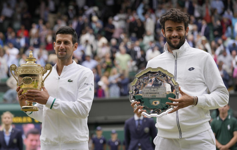 Serbia's Novak Djokovic, left holds the winners trophy after he defeated Italy's Matteo Berrettini who holds his runners-up plate as they pose for a photograph following the men's singles final on day thirteen of the Wimbledon Tennis Championships in London, Sunday, July 11, 2021. (AP Photo/Kirsty Wigglesworth)
