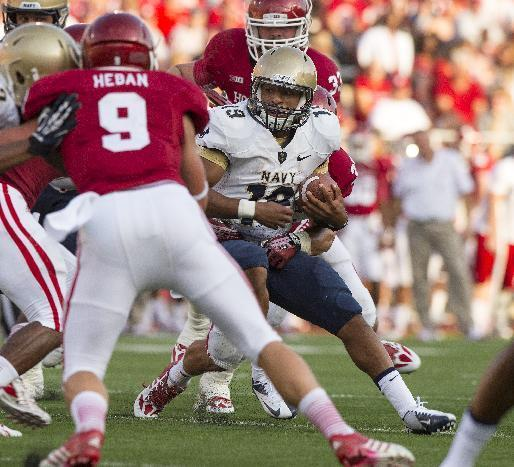 Navy quarterback Keenan Reynolds (19) is brought down by a host of Indiana defenders during the first half of an NCAA college football game, Saturday, Sept. 7, 2013, in Bloomington, Ind. (AP Photo/Doug McSchooler)