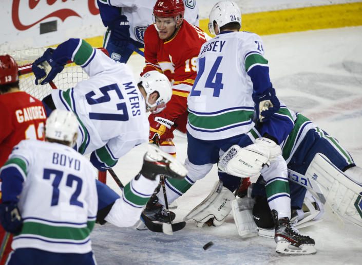 Vancouver Canucks' Tyler Myers, left, and Jimmy Vesey, right, try to keep Calgary Flames' Matthew Tkachuk away from the puck during the first period of an NHL hockey game Thursday, May 13, 2021, in Calgary, Alberta. (Jeff McIntosh/The Canadian Press via AP