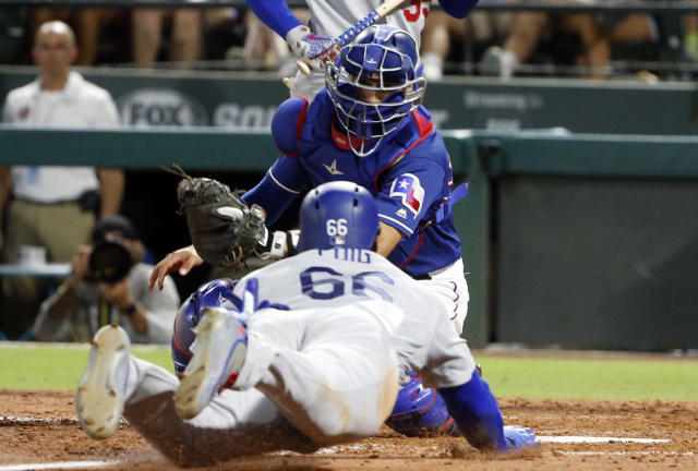 Texas Rangers catcher Isiah Kiner-Falefa (9) tags out Los Angeles Dodgers' Yasiel Puig, who tried to steal home during the seventh inning of a baseball game Wednesday, Aug. 29, 2018, in Arlington, Texas. (AP Photo/Michael Ainsworth)