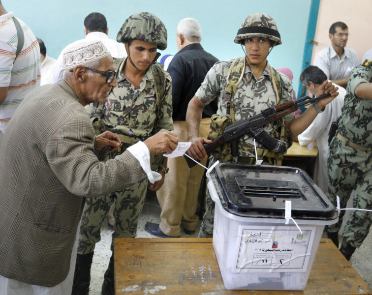 An Egyptian casts his vote in front of soldiers at a polling station in Zagazig, 63 miles (100 kilometers) northeast of Cairo, Egypt, Saturday, June 16, 2012. Egyptians voted Saturday in the country's landmark presidential runoff, choosing between Hosni Mubarak's ex-prime minister and an Islamist candidate from the Muslim Brotherhood after a race that has deeply polarized the nation. The two-day balloting will produce Egypt's first president since a popular uprising last year ousted Mubarak, who is now serving a life sentence. (AP Photo/Amr Nabil)