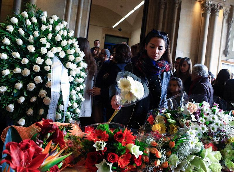 A woman puts flowers at the mourning hall for the victims of Sunday's fatal bus accident, at the University of Barcelona on March 21, 2016 in Barcelona (AFP Photo/Pau Barrena)
