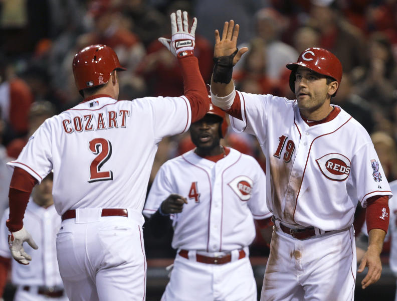 Cincinnati Reds' Zack Cozart (2) is congratulated by Joey Votto (19) after Cozart hit a three-run home run off Washington Nationals starting pitcher Dan Haren in the third inning of a baseball game, Friday, April 5, 2013, in Cincinnati. It was the second home run of the game for Cozart. (AP Photo/Al Behrman)