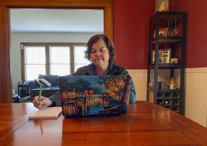 """In this March 27, 2020, photo, Lisa Kaenzig, dean of William Smith College, works from her home while following coronavirus Stay-at-Home guidelines in Geneva, N.Y. The world generally has been a place where extroverts are rewarded and introverts get a side-eye, says Kaenzig. """"All of the things that make the world harder for them as introverts, the world is better for them right now. They're adapting much more quickly,"""" she says. (Morgan Kaenzig de Denus via AP)"""
