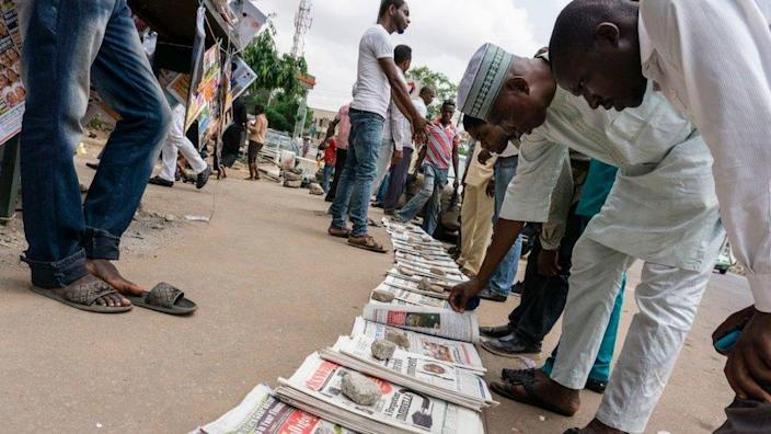 People read newspapers sold in the streets, which front pages focusing on Nigeria's President follow-up medical consultation in London and the release of eighty-two girls from Chibok, in Abuja on May 8, 2017