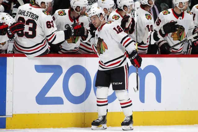 Chicago Blackhawks left wing Alex DeBrincat, front, is congratulated as he passes the team box after scoring a goal against the Colorado Avalanche in the first period of an NHL hockey game Saturday, Dec. 29, 2018, in Denver. (AP Photo/David Zalubowski)