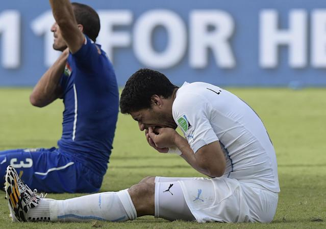 Uruguay forward Luis Suarez (R) puts his hand to his mouth after clashing with Italy's defender Giorgio Chiellini during a Group D football match between Italy and Uruguay at the Dunas Arena in Natal during the 2014 FIFA World Cup on June 24, 2014 (AFP Photo/Daniel Garcia)