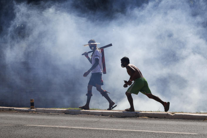 Indigenous clashing with police walk through clouds of tear gas outside Congress in Brasilia, Brazil, Tuesday, June 22, 2021. Indigenous who are camping in the capital to oppose a proposed bill they say would limit recognition of reservation lands clash with police who blocked them from entering Congress. (AP Photo/Eraldo Peres)