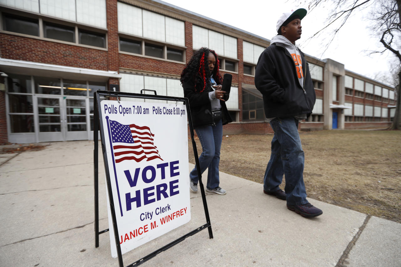 Voters leave a polling location at Bow Elementary in Detroit, Tuesday, March 10, 2020. (AP Photo/Paul Sancya)