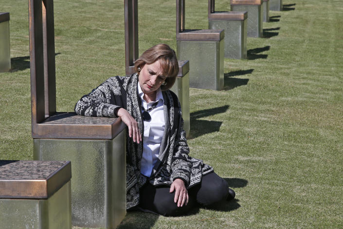 Lynne Gist sits next to her sister's memorial in the Field of Empty Chairs at the Oklahoma City National Memorial and Museum, Wednesday, April 15, 2020, in Oklahoma City. The site is made up of 168 empty chairs representing those who lost their lives, with their name etched in the glass base. (AP Photo/Sue Ogrocki)
