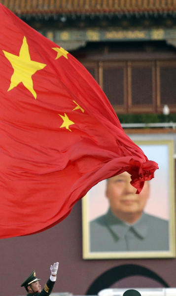 A Chinese paramilitary policeman raises a Chinese national flag at a flag-raising ceremony in the early morning Wednesday, Nov. 14, 2012 at Tiananmen Square near the Great Hall of the People, where the closing ceremony for the 18th Communist Party Congress will be held, in Beijing, China. (AP Photo/Lee Jin-man)