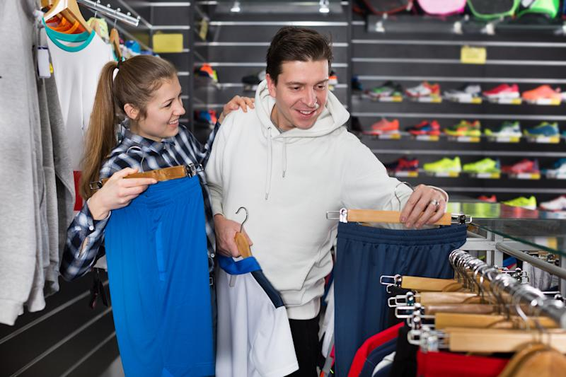 Man and woman shopping at an athletic fashion retail store.