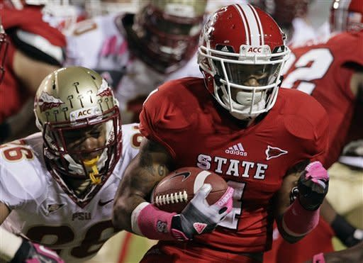 North Carolina State's Tobais Palmer runs the ball as Florida State's P.J. Williams (26) tries to make the tackle during the first half of an NCAA college football game in Raleigh, N.C., Saturday, Oct. 6, 2012. (AP Photo/Gerry Broome)