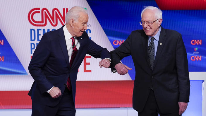 Former Vice President Joe Biden, left, and Sen. Bernie Sanders, I-Vt., right, greet one another before they participate in a Democratic presidential primary debate at CNN Studios in Washington on March 15, 2020. (Evan Vucci/AP)