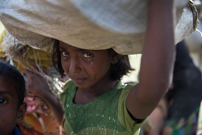 <p>A Rohingya girl cries as refugees fleeing from Myanmar cross a stream in the hot sun on a muddy rice field near Palang Khali, Cox's Bazar, Bangladesh, on October 16, 2017. (Photograph by Paula Bronstein/Getty Images) </p>