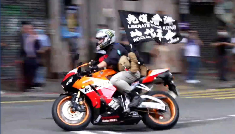 """FILE - In this Wednesday, July 1, 2020, file image made from video, motorcyclist Tong Ying-kit carries a flag reading """"Liberate Hong Kong, Revolution of our times"""" during a protest in Hong Kong on the anniversary of its return to China. Tong has been sentenced to nine years in prison in the closely watched first case under Hong Kong's national security law as Beijing tightens control over the territory. (Cable TV Hong Kong via AP)"""