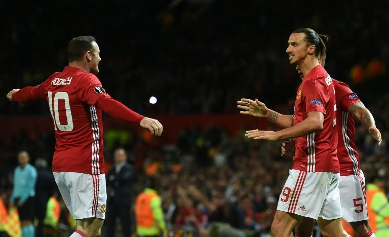 Manchester United's striker Zlatan Ibrahimovic (R) celebrates scoring his team's first goal with Manchester United's striker Wayne Rooney (L) during the UEFA Europa League group A football match between Manchester United and Zorya Luhansk