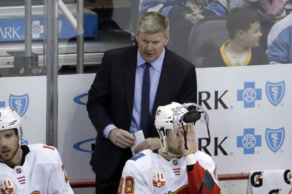 Calgary Flames head coach Bill Peters stands behind Andrew Mangiapane (88) during the third period of an NHL hockey game against the Pittsburgh Penguins in Pittsburgh, Monday, Nov. 25, 2019. The Penguins won in overtime 3-2. (AP Photo/Gene J. Puskar)