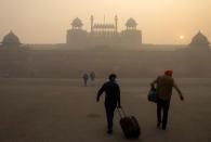 People arrive to visit the Red Fort on a smoggy morning in the old quarters of Delhi