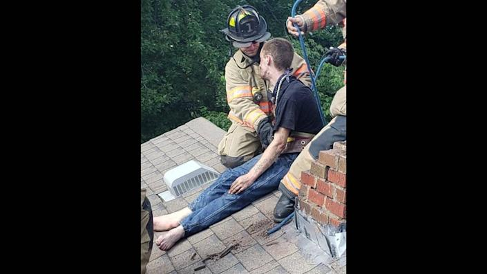 A barefoot Cody Methanial Sargent sits atop a house after trying to escape police through a chimney. Photo from Vanderburgh County Sheriff's Office.