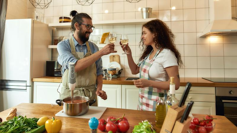 Italian man looking at his girlfriend while they are toasting, drinking white wine. Chef cook using hand blender, preparing a meal in the kitchen. Cooking at home, Italian cuisine. Web Banner