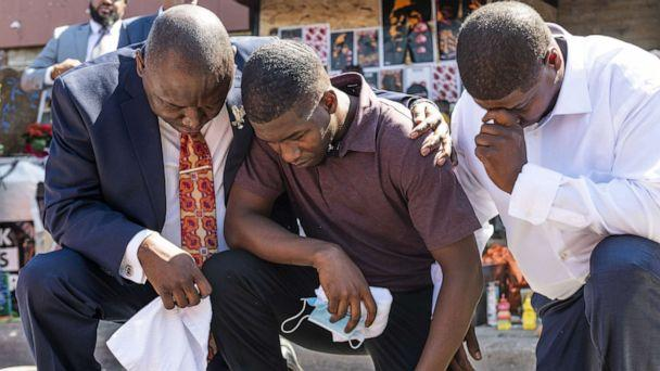 PHOTO: Quincy Mason Floyd, center, son of George Floyd, and attorney Ben Crump, left, kneel at the site where George Floyd was killed, on June 3, 2020, in Minneapolis, Minn. (Stephen Maturen/Getty Images)