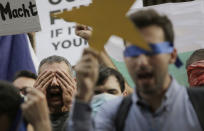 "Protesters shout ""Resignation"" and keep their eyes closed in front of the German Embassy in Sofia, Bulgaria, Wednesday, Aug. 12, 2020. Several hundred anti-government protesters gathered on Wednesday in front of Germany's embassy in Sofia, calling on Berlin and Brussels to ""open their eyes"" to widespread corruption in Bulgaria. Demands for the resignations of Bulgarian Prime Minister Boyko Borissov and the country's chief prosecutor, Ivan Geshev, have been at the core of month-long street protests in the capital and other big cities in the Balkan country. (AP Photo/Valentina Petrova)"
