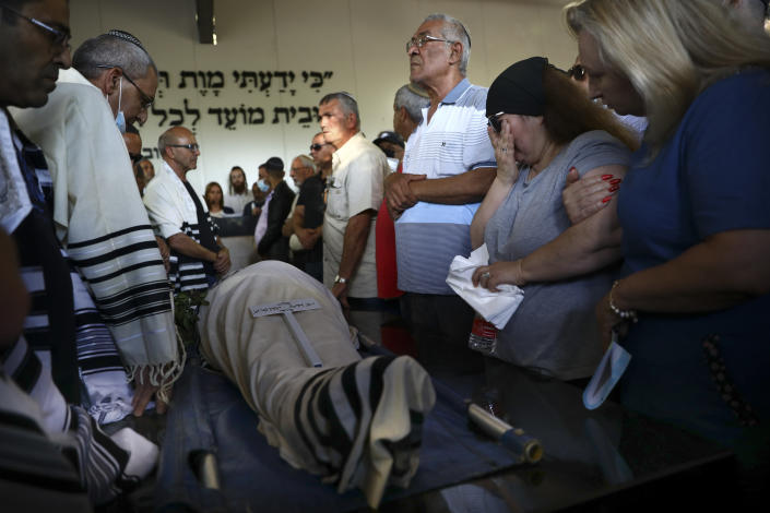 Mourners attend the funeral of Yigal Yehoshua, 56, at a cemetery in Hadid, central Israel, Tuesday, May 18, 2021. Yehoshua died of wounds sustained when his car was pelted with rocks during Israeli Arab riots in the Israeli city of Lod on May 11. (AP Photo/Oded Balilty)