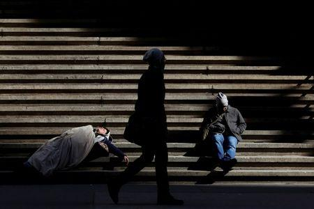 A homeless person sleeps on the steps of Federal Hall on Wall St. in New York City