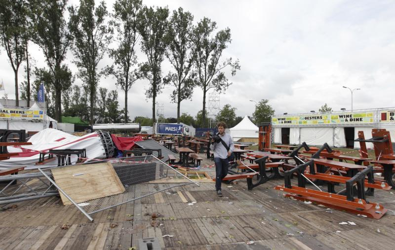 A man walks through the damaged site of the festival campsite near Hasselt, 50 miles (80 kilometers) east of Brussels, Friday Aug. 19, 2011. Five people died in a fierce thunderstorm on Thursday, that mangled tents and downed trees and scaffolding at the open-air music festival PukkelPop in Belgium. Organizers canceled the annual four-day festival. (AP Photo/Yves Logghe)