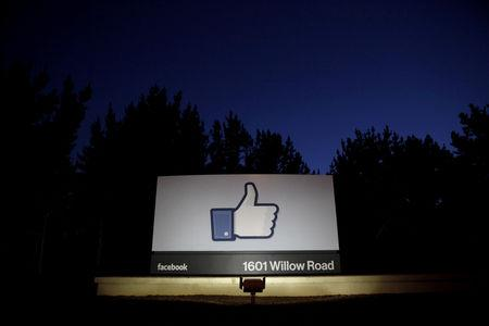 FILE PHOTO: The sun rises behind the entrance sign to the Facebook headquarters in Menlo Park