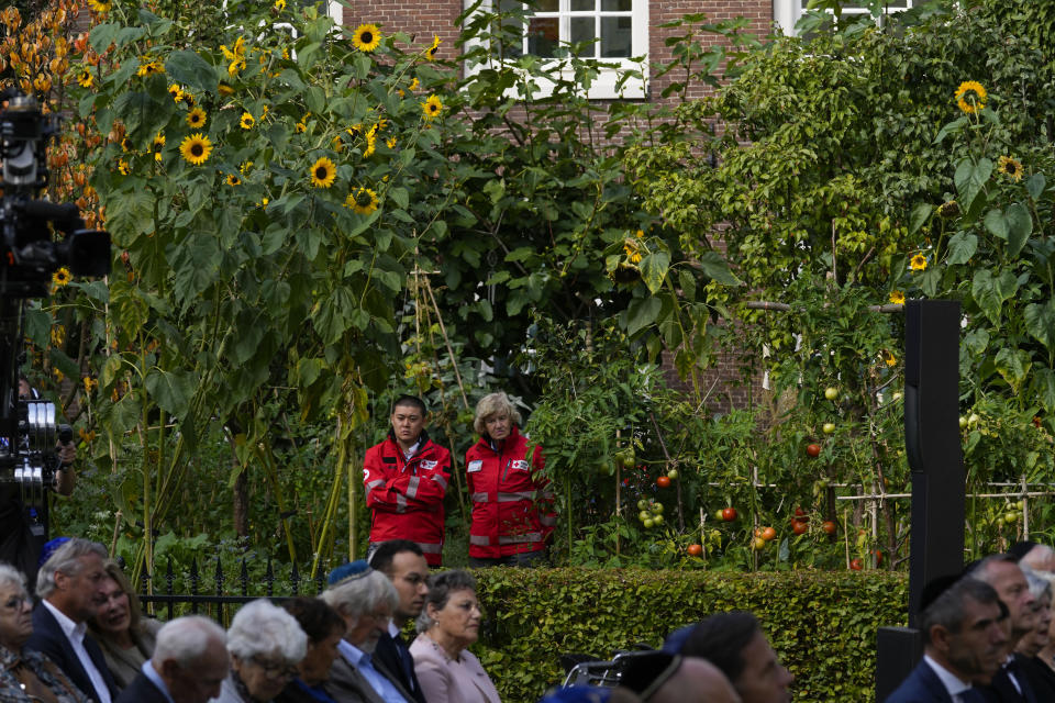 """Rescue workers watch a ceremony where King Willem-Alexander officially unveiled a new monument in the heart of Amsterdam's historic Jewish Quarter on Sunday, Sept. 19, 2021, honoring the 102,000 Dutch victims of the Holocaust. Designed by Polish-Jewish architect Daniel Libeskind, the memorial is made up of walls shaped to form four Hebrew letters spelling out a word that translates as """"In Memory Of."""" The walls are built using bricks each of which is inscribed with the name of one of the 102,000 Jews, Roma and Sinti who were murdered in Nazi concentration camps during World War II or who died on their way to the camps. (AP Photo/Peter Dejong)"""