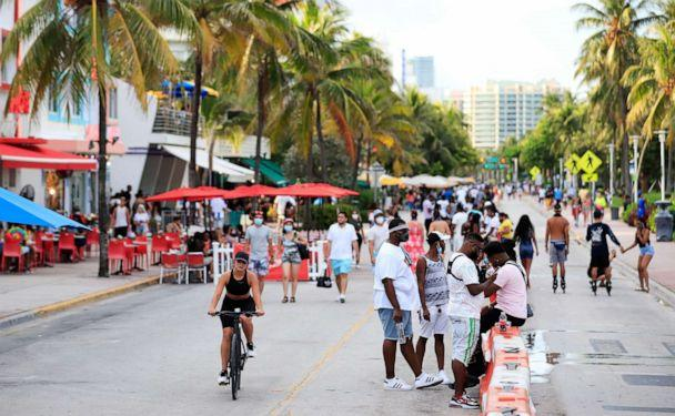 PHOTO: A woman rides her bike past pedestrians on Ocean Drive on July 3, 2020 in the South Beach neighborhood of Miami Beach, Fla. (Cliff Hawkins/Getty Images)