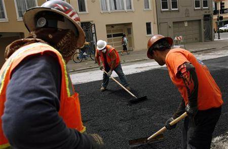 Workers spread asphalt on street in San Francisco