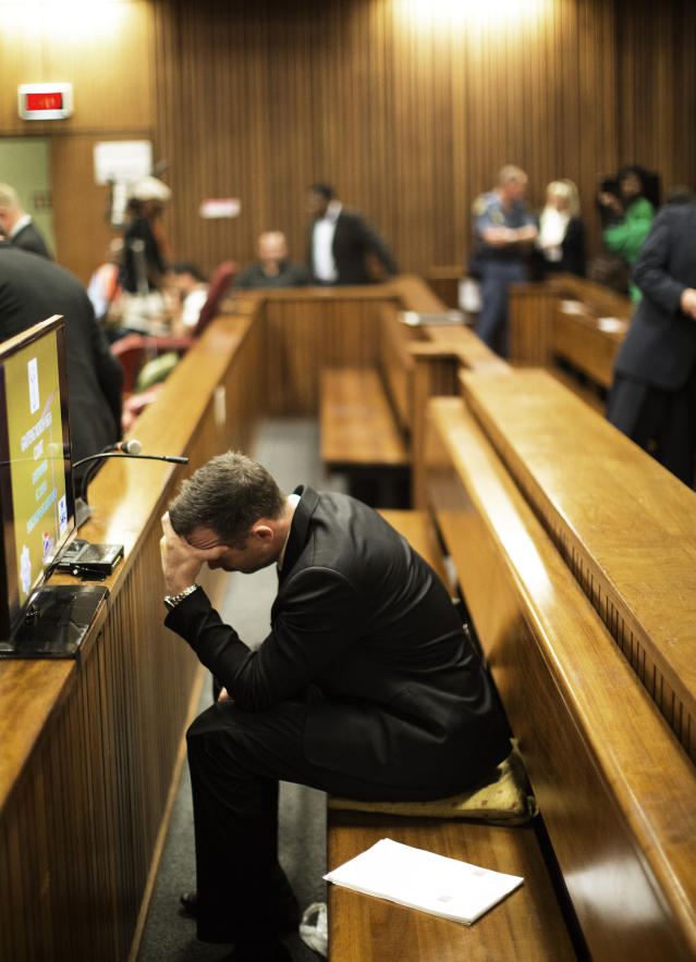 Oscar Pistorius, puts his hands to his head in court on the fourth day of his trial at the high court in Pretoria, South Africa, Thursday, March 6, 2014. Pistorius is charged with murder for the shooting death of his girlfriend, Reeva Steenkamp, on Valentines Day in 2013. (AP Photo/Marco Longari, Pool)