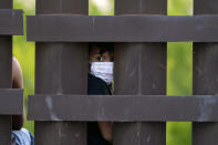 FILE - In this March 21, 2021, file photo, a migrant child peeks through the U.S.-Mexico border metal wall as a group of migrants is processed and taken into custody while trying to sneak across the border in Abram-Perezville, Texas. For the third time in seven years, U.S. officials are scrambling to handle a dramatic spike in children crossing the U.S.-Mexico border alone, leading to a massive expansion in emergency facilities to house them as more kids arrive than are being released to close relatives in the United States. (AP Photo/Julio Cortez, File)