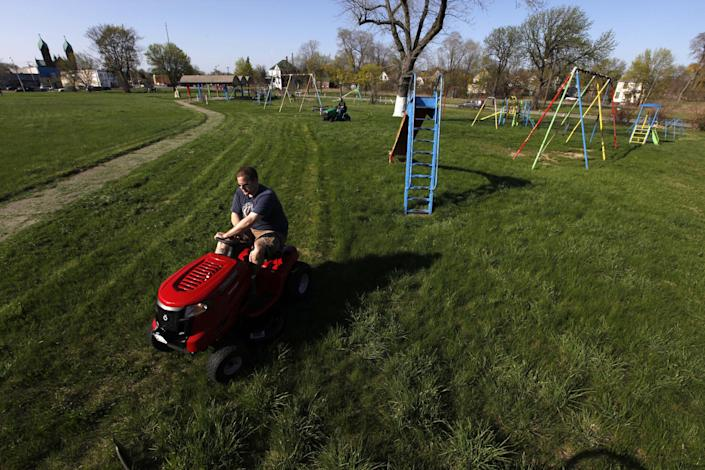 Mower Gang member Nathan Labadie, of Commerce Township mows at Duweke Park in Detroit, Wednesday May 1, 2013. The Mower Gang, a group of volunteer lawn mower riders, adopt parks beginning in the spring and keep them free of high-grass throughout the summer. (AP Photo/Paul Sancya)