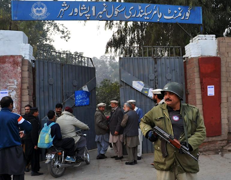 A policeman stands guard outside a government school after schools in the city reopened on January 12, 2015 following a Taliban attack in Peshawar (AFP Photo/Hasham Ahmed)