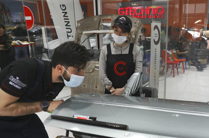 Female trainee Farahnaz Deravi watches a man repair a car door at a detailing shop in Tehran, Iran, Sunday, April 18, 2021. The auto industry remains male-dominated around the world, let alone in the tradition-bound Islamic Republic. Still Iranian women, especially in the cities, have made inroads over the years. (AP Photo/Vahid Salemi)