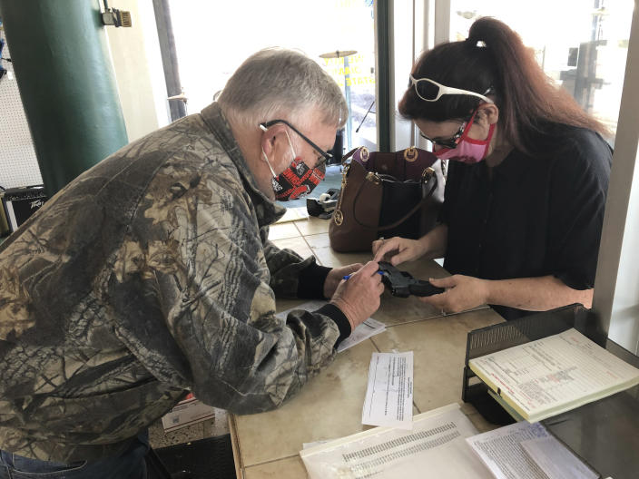 """In this April 9, 2021, photo, Terry Stephens, left, a sales worker at Ritchies Pawn Central, a store that was mentioned in J.D. Vance's book """"Hillbilly Elegy"""", talks with Laura Stephens. Laura, who is no relation to Terry, was asking about a 9mm Taurus handgun she bought. She says her home has been broken into 4 times. Vance, whose book helped explain to the nation Donald Trump's popularity among the Appalachian working class, is """"thinking seriously"""" about running for the U.S. Senate seat Republican two-term incumbent Rob Portman decided against seeking again in 2022. (AP Photo/Dan Sewell)"""