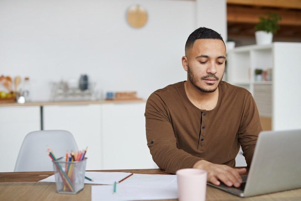 Portrait of man using laptop while working in home interior, copy space