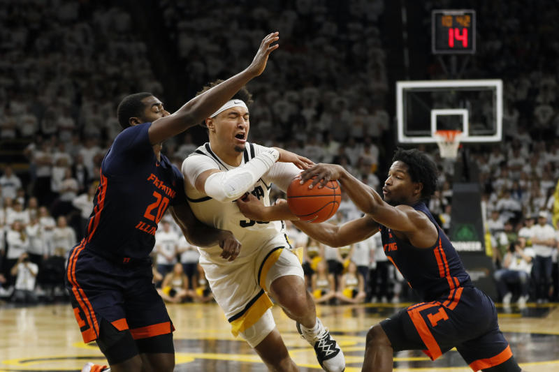 Iowa forward Cordell Pemsl, center, drives between Illinois' Da'Monte Williams, left, and Andres Feliz, right, during the second half of an NCAA college basketball game, Sunday, Feb. 2, 2020, in Iowa City, Iowa. (AP Photo/Charlie Neibergall)