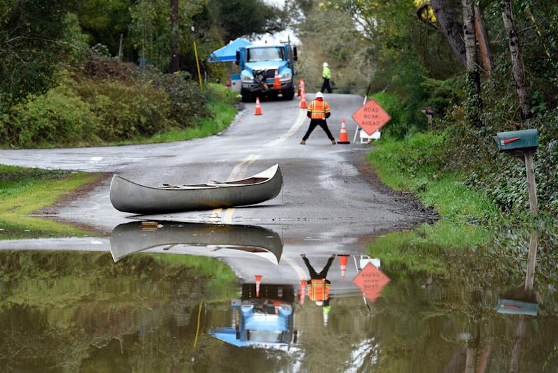 Pacific Gas & Electric workers and a canoe are seen on a street flooded by the Russian River in Forestville, Calif., on Feb. 27, 2019. (Photo: Michael Short/AP)