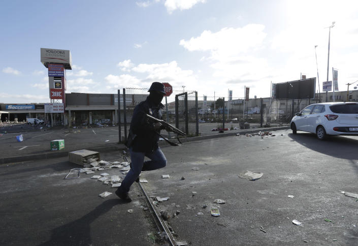 A security officer pursues looters at a shopping centre in Vosloorus near Johannesburg, Tuesday July 13, 2021. South Africa's rioting continued Tuesday with the death toll rising to 32 as police and the military struggle to quell the violence in Gauteng and KwaZulu-Natal provinces. The violence started in various parts of KwaZulu-Natal last week when Zuma began serving a 15-month sentence for contempt of court. (AP Photo/Themba Hadebe)